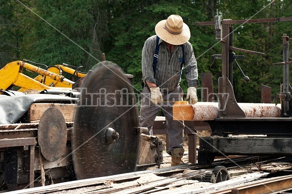 Man operating a circular saw mill on the farm