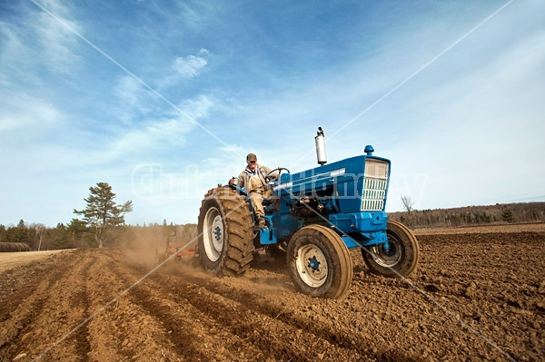 Farmer driving tractor working up field with cultivator