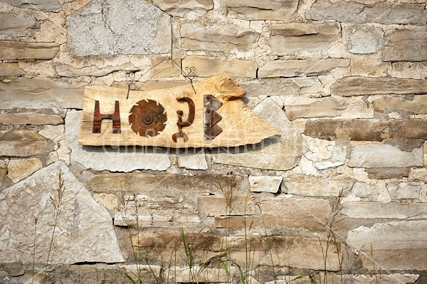 Hand made Hope garden art sign hanging on a barn stone wall