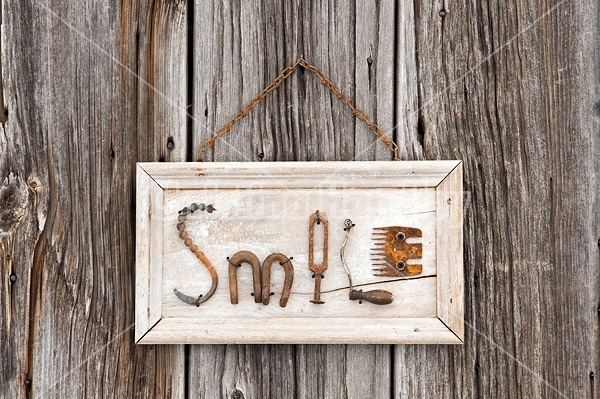 Hand crafted Smile art sign made out of wood and recycled or repurposed farm tools and machinery parts
