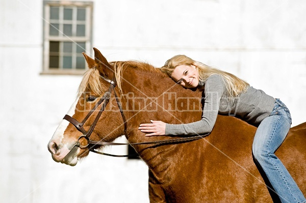 Young woman riding Belgian horse bareback.