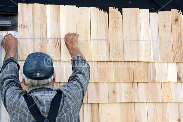 Man putting cedar shingles on the wall of a barn