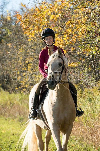 Young woman riding palomino horse
