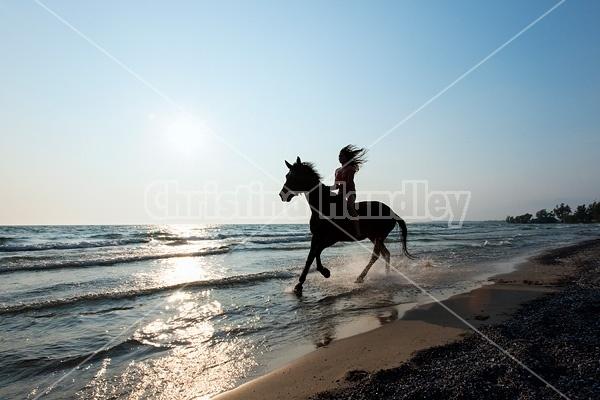 Silhouette photo of woman riding a horse bareback.