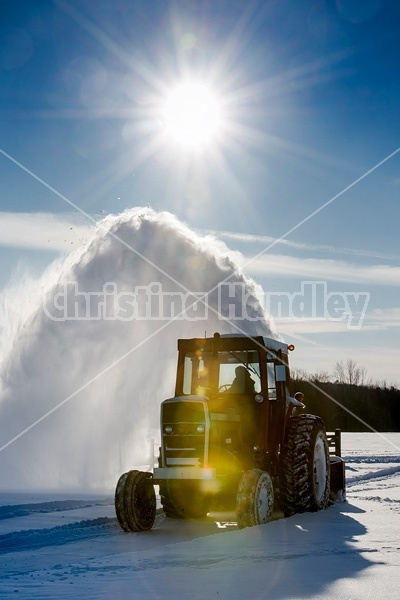 Farmer blowing snow