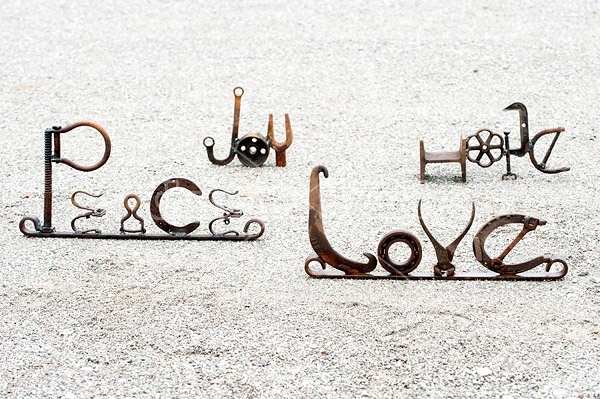 Hand crafted art signs made out of recycled and repurposed farm tools and machinery parts then welded together