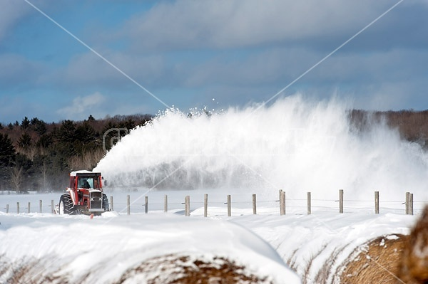 Snow blowing a road with tractor