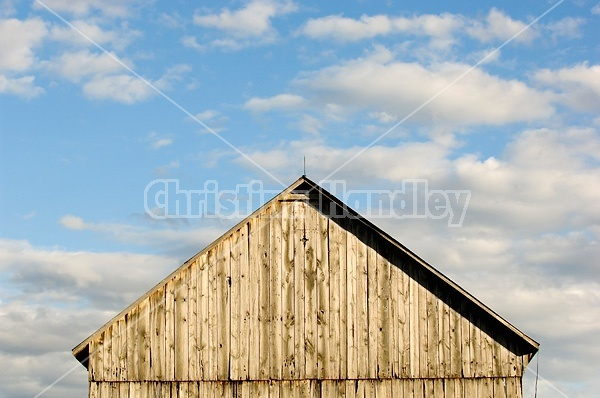 Barn pictured against big blue sky with puffy clouds