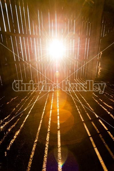 Rays of sunshine beaming through barn boards