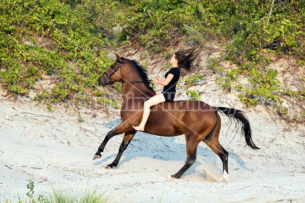 Young woman riding a hrose bareback in the sand