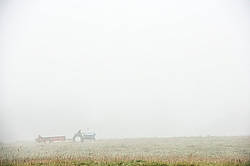 Spreading manure in the early morning fog