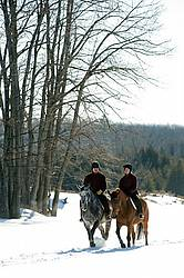 Husband and wife horseback riding through the deep snow