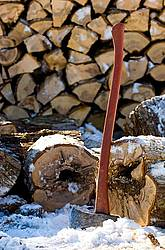 Splitting axe leaning against firewood that is cut, split and piled.