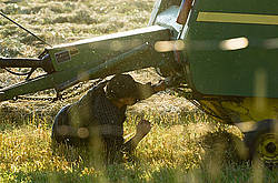 Farmer working underneath round baler to get the twine re-threaded.