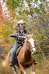 Young woman riding Paint horse