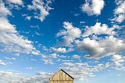 Barn pictured against big blue sky with white puffy clouds