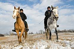 Two women horseback riding in the winter