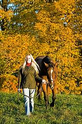 Woman with horse in pasture
