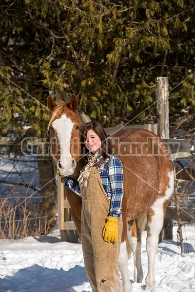 Young woman standing and hugging her horse