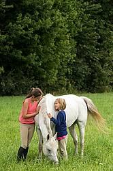 Potrait of two girls with a gray pony