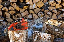 Firewood cut, split and piled with chainsaw sitting on wood block