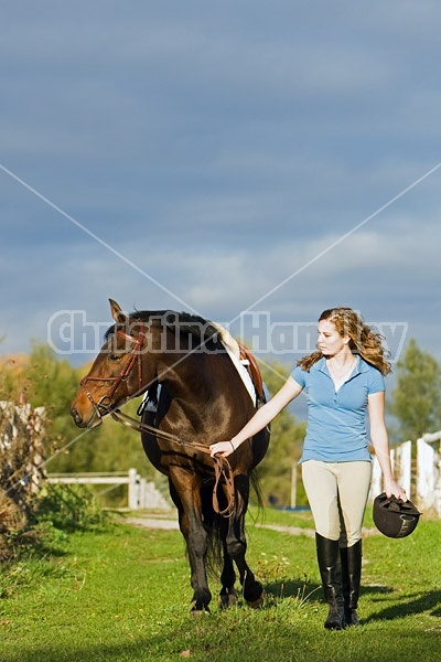 Young girl leading her horse down a grass path
