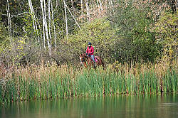 Woman horseback riding around pond in the autumn colors