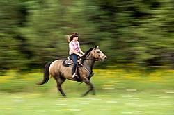 Young woman horseback riding western, galloping along field