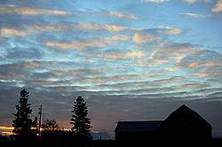 Silhouette photo of barn against colorful sky