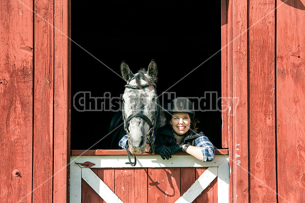 Young woman in barn doorway with horse
