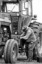 Farmer performing maintenance on tractor