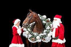 Santa Claus and Mrs Claus standing with a thoroughbred horse with a Christmas wreath over its head.