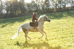 Young woman riding palomino horse