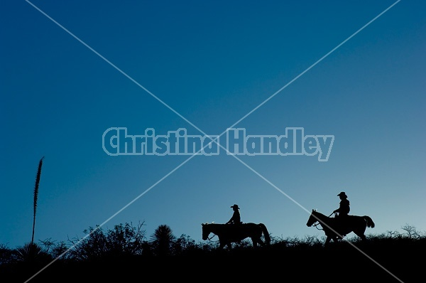 Two western riders silhouetted along a ridge top at sunset