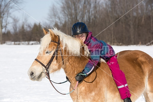 Young girl riding her pony bareback in the winter.