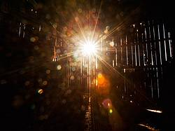 Starburst of sunlight shining in through the barn boards of an old barn
