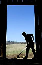 Farm woman silhouetted in barn doorway