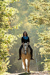 Woman riding a palomino horse
