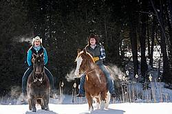 Two young woman riding horses bareback through deep snow