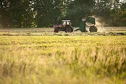 Farmer baling round bales of hay