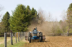 Farmer driving tractor pulling a land roller