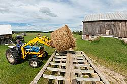 Farmer unloading round bales of straw from hay wagon with a front end loader tractor