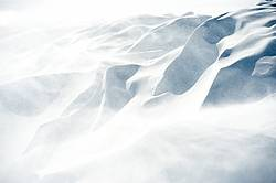 Photo of wind blowing over snow drift
