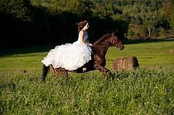 Woman riding horse wearing a wedding dress