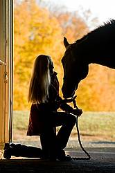 Silhouette of woman and horse in barn door