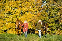 Two women leading horses through field.