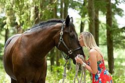 Young woman with her dark bay horse