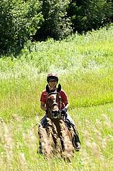 Woman horseback riding in field