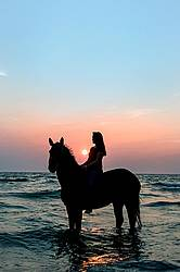 Silhouette photo of woman riding a horse bareback.