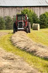 Farmer round baling hay
